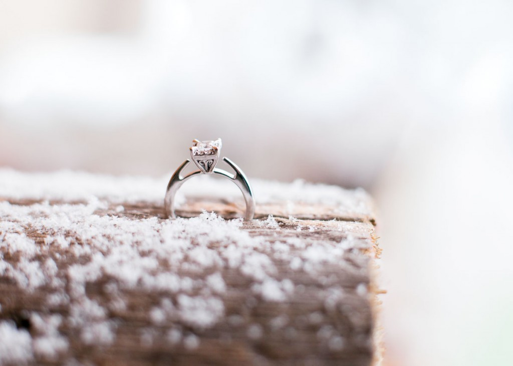 Diamond engagement ring on snow covered log