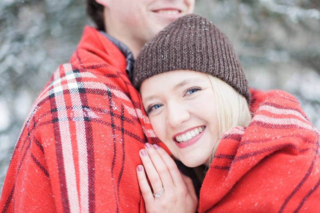 Engaged couple cuddle beneath a blanket in laramie wyoming