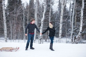 Engaged couple with vintage sled in Laramie wyoming