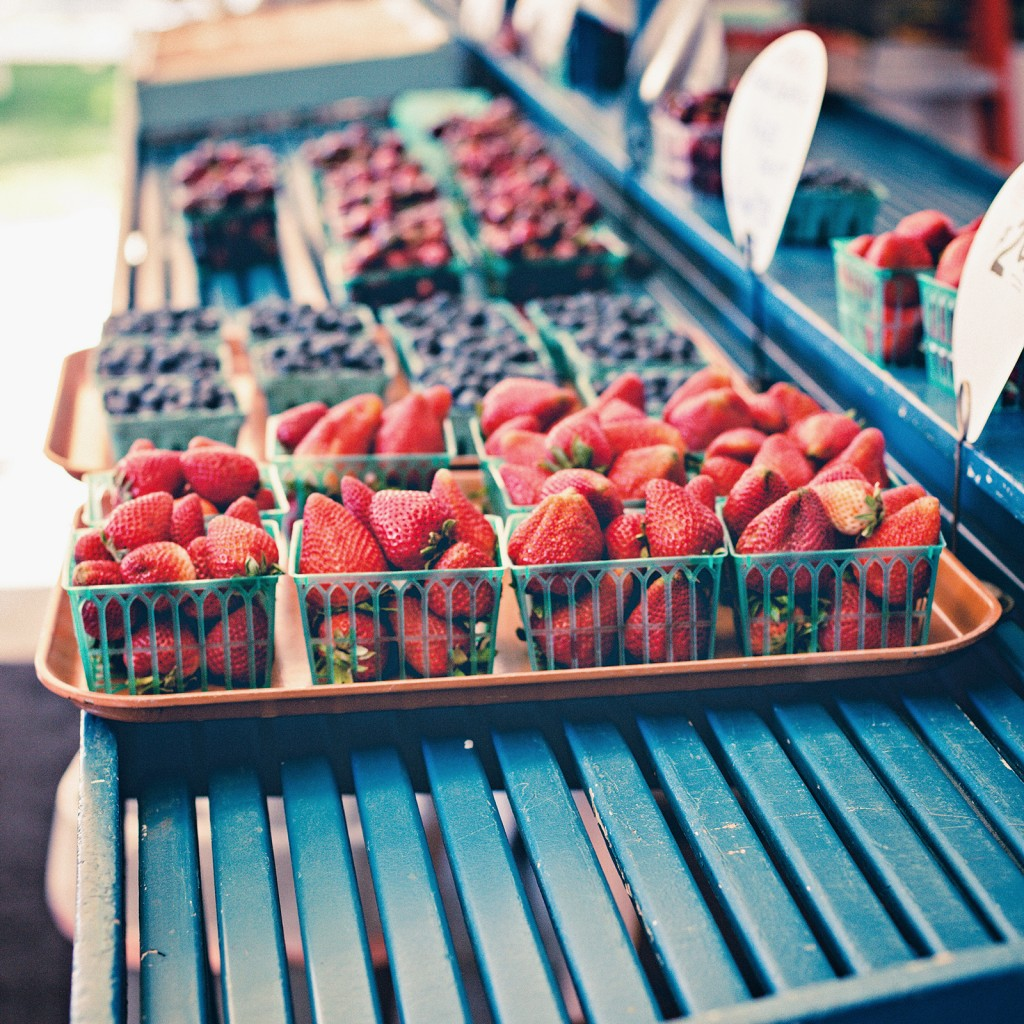 Cherries, strawberries, and blueberries on a blue shelf in a farmers market in waterloo, CA.