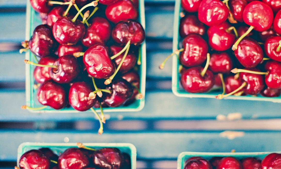 Epic photograph of cherries on a blue shelf in a farmers market in waterloo, CA.