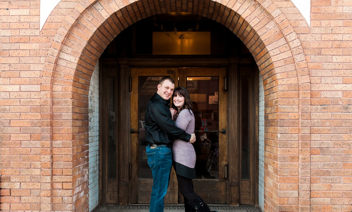 Couple under historic archway, couples photography in downtown Laramie Wyoming.