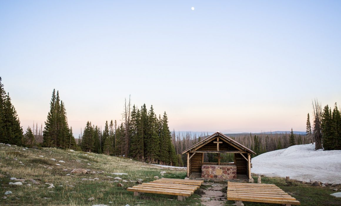 The last light of sunset and a full moon glows over the St Alban's wedding Chapel in The Snowy Range Mountains of Medicine Bow National Forest near Laramie, Wyoming.